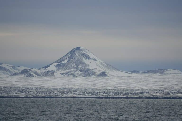 iceland explorer day trips photo - shows perfect cone shaped mountain on the reykjanes peninsular in iceland, all covered in snow
