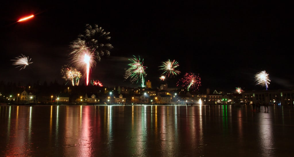 Fireworks along the Reykjavik harborside are reflectic in the inky black, totally calm water.
