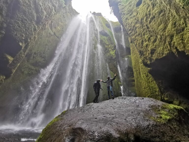 waterfalls reykjavikTwo people stand on a massive rock at the bottom of a waterfall in Iceland