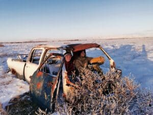 quality airport transfer in winter - not in this car. The photo is of two people in an obviously abandoned car that is rusted with plants growing out of it!