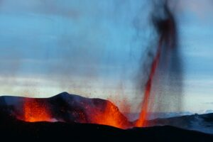 Volcanoes exploding. Lave being spewed up in a line from a crack.