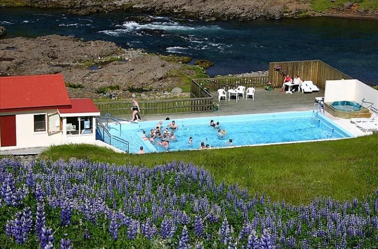 Photo of swimming pool set into the icelandic landscape.