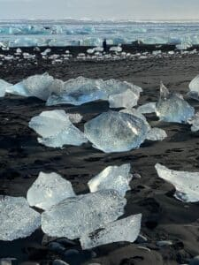 Photograph of diamond beach, a black sand beach in the south of iceland that is covered by large and small icebergs. The icebergs come from the nearby glacial face. The ice looks slightly blue.