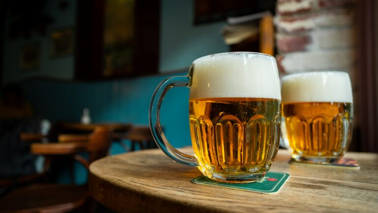 a pint of beer with way to much foam sits on a bar table, presumably to be drunk on beer day in Iceland.