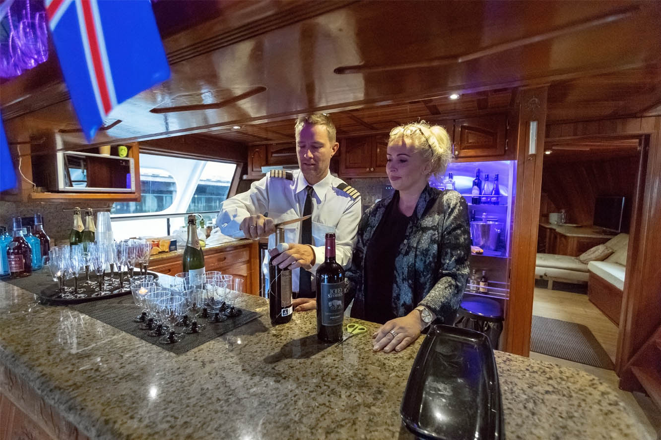 The captain and a customer behind the bar on the superyacht Amelia Rose